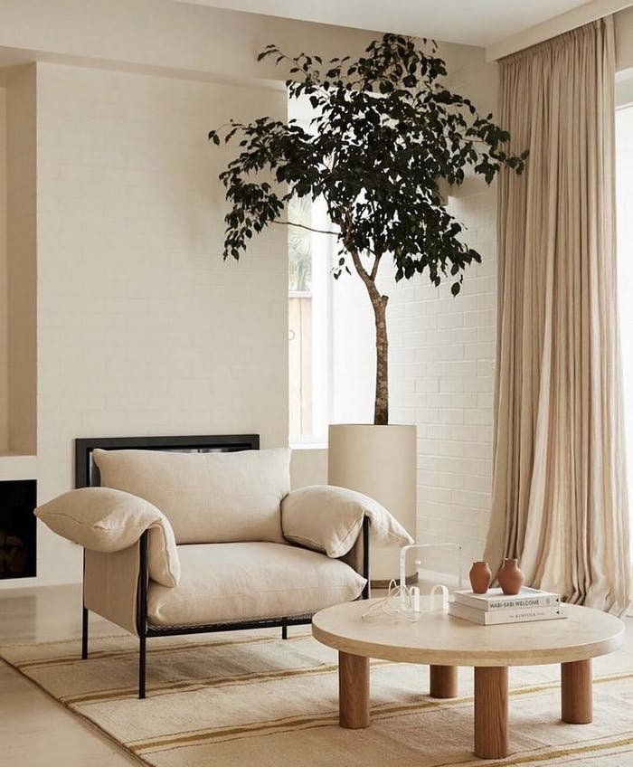 "Cozy corner in a living room, created next to a window with a soft armchair and a tall tree.<span class=""sr-only""> (opened in a new window/tab)</span>"