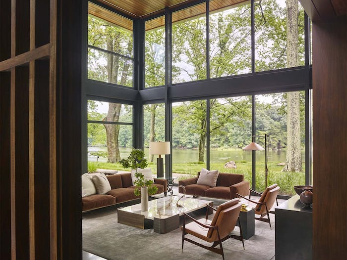 "Earthy living room with a stunning view of a lakeside.<span class=""sr-only""> (opened in a new window/tab)</span>"