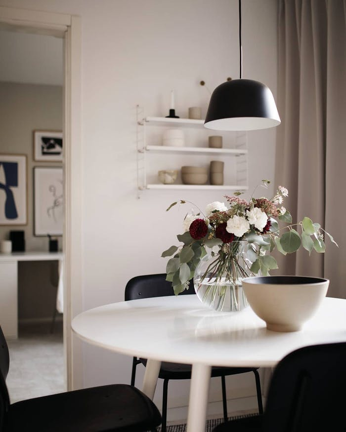 "Minimal dining table with a vase of flowers as centrepiece.<span class=""sr-only""> (opened in a new window/tab)</span>"