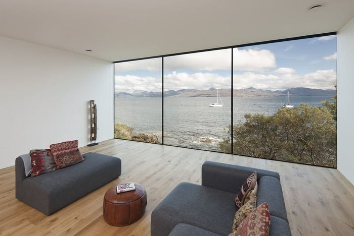 "Living room with a full-wall window looking into the sea.<span class=""sr-only""> (opened in a new window/tab)</span>"