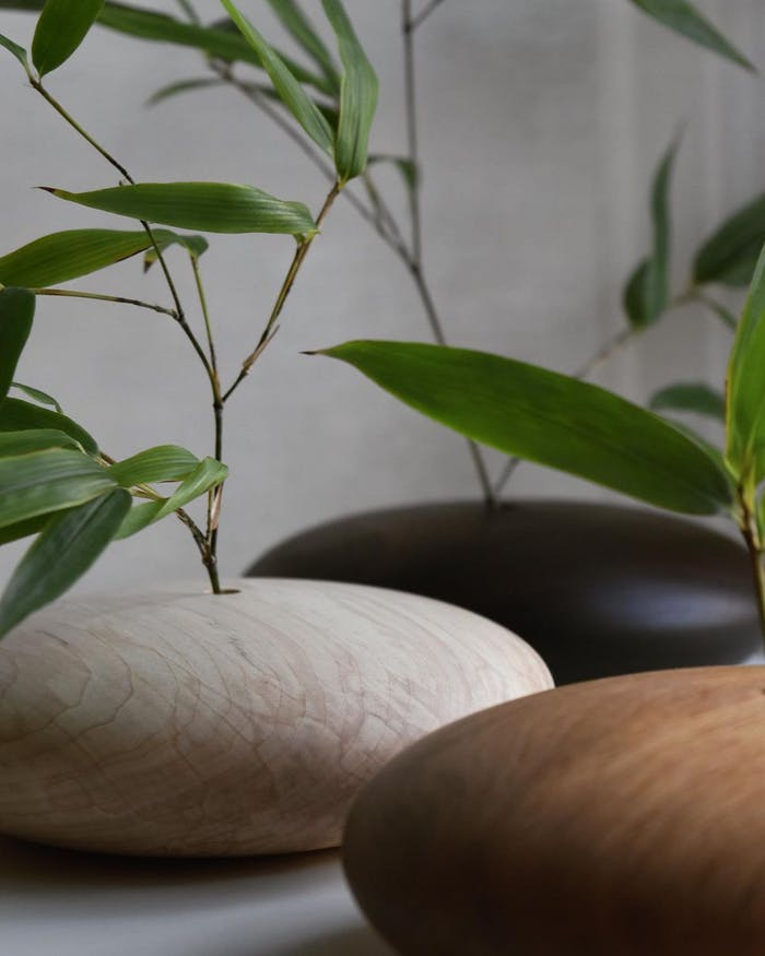 """Simple greenery arrangement on pebble shaped wood vases.<span class=""""sr-only""""> (opened in a new window/tab)</span>"""