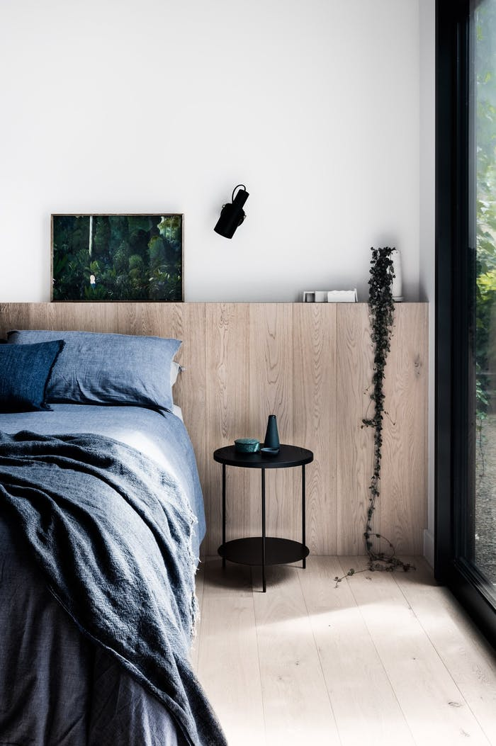 """Bedroom with side windows looking into the green surroundings.<span class=""""sr-only""""> (opened in a new window/tab)</span>"""