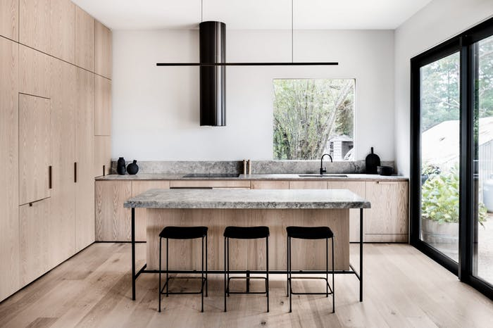 """View of the kitchen: wood floor and cabinets with island in the middle.<span class=""""sr-only""""> (opened in a new window/tab)</span>"""