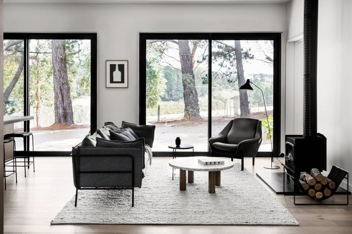 """Contemporary living room with sofa, armchair and a wood stove.<span class=""""sr-only""""> (opened in a new window/tab)</span>"""