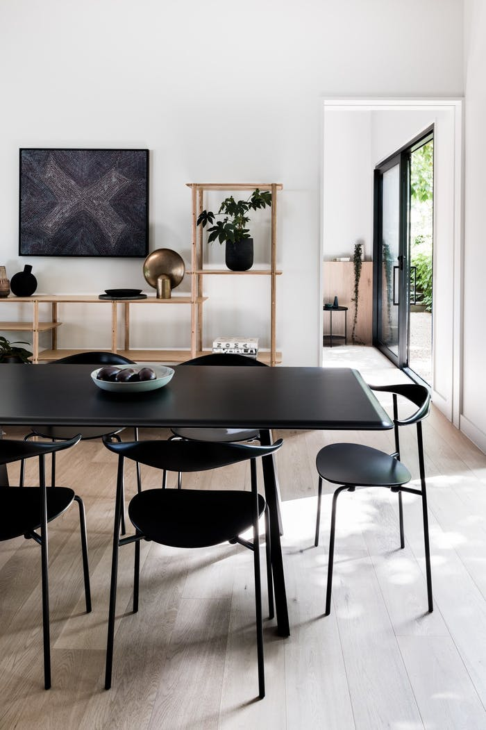 """Side view of the open area showing the dining table and the bedroom in the background.<span class=""""sr-only""""> (opened in a new window/tab)</span>"""