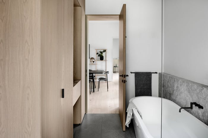 """Small bathroom with grey floor, wood cabinets and free-standing bathtub.<span class=""""sr-only""""> (opened in a new window/tab)</span>"""