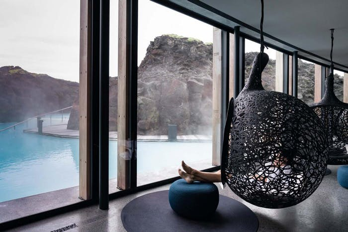 """Hanging chairs looking into a beautiful thermal pool.<span class=""""sr-only""""> (opened in a new window/tab)</span>"""