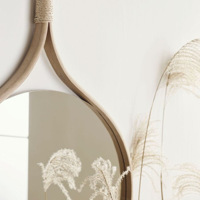 """Curved mirror with a wooden frame reflecting flowers.<span class=""""sr-only""""> (opened in a new window/tab)</span>"""