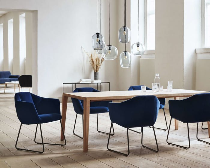 """Dining room flooded with natural light, with light wood floors and walls and blue accent dining chairs.<span class=""""sr-only""""> (opened in a new window/tab)</span>"""