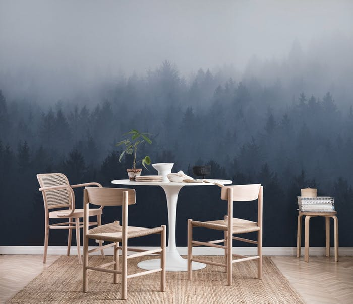 """Dining room with light wood furniture and a blue mural showing a foggy forest.<span class=""""sr-only""""> (opened in a new window/tab)</span>"""