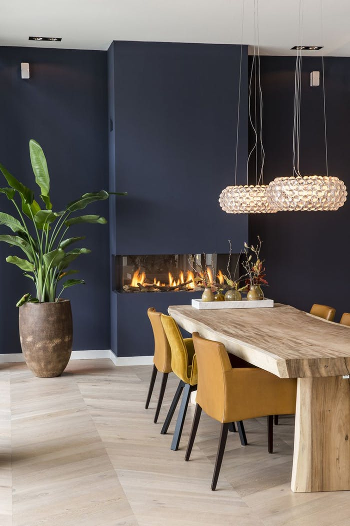 """Dining room with blue wall, rustic wood table and big fireplace.<span class=""""sr-only""""> (opened in a new window/tab)</span>"""