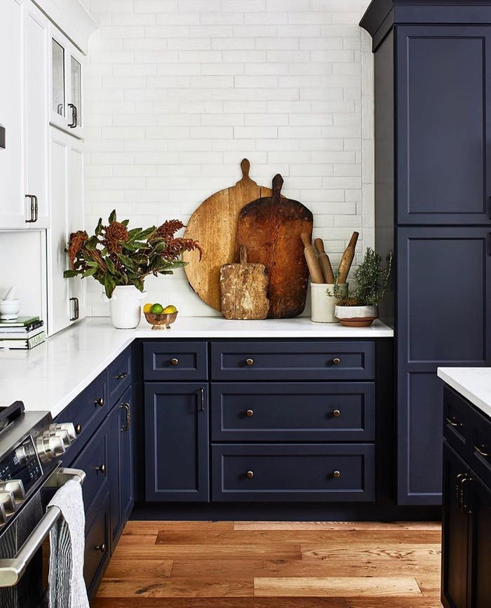 """Kitchen with blue cabinets, and rustic wood cutting boards and flowers as decor.<span class=""""sr-only""""> (opened in a new window/tab)</span>"""