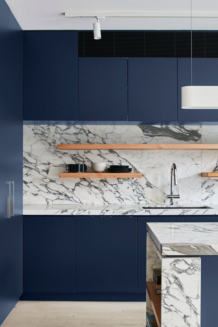 """Kitchen with blue cabinets and a contrasting clear stone backsplash.<span class=""""sr-only""""> (opened in a new window/tab)</span>"""