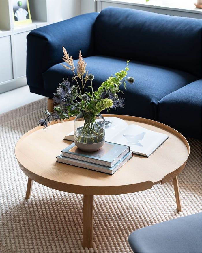 """Close-up of a blue sofa and a bunch of flowers over a light wood coffee table.<span class=""""sr-only""""> (opened in a new window/tab)</span>"""