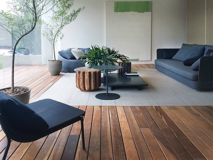 """Living area with blue sofas, dark wood floor and full-height windows with invisible profiles.<span class=""""sr-only""""> (opened in a new window/tab)</span>"""