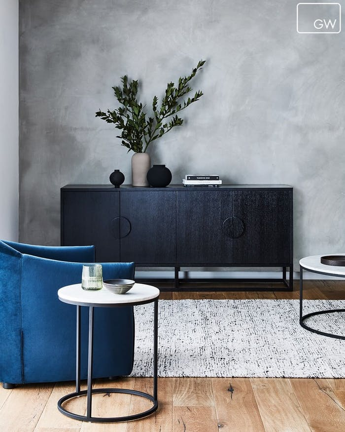 """Living area with grey, white and black palette and one accent blue armchair.<span class=""""sr-only""""> (opened in a new window/tab)</span>"""