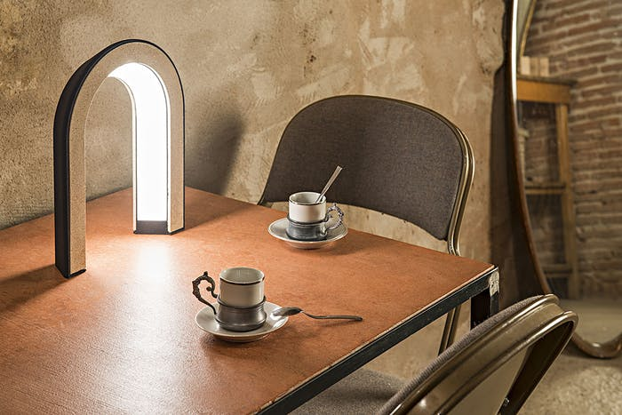 """Arc-shaped lamp made with coffee grounds, sitting on a table.<span class=""""sr-only""""> (opened in a new window/tab)</span>"""