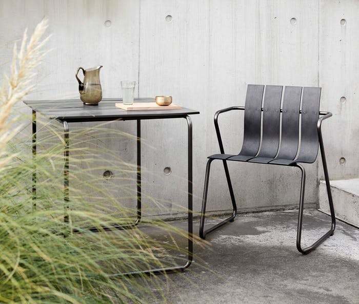 """Sustainable plastic chair styled outdoors with a table on the side.<span class=""""sr-only""""> (opened in a new window/tab)</span>"""