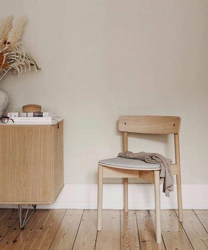 """Front view of a sustainable wood chair styled with a blanket on top and a dresser with books and dry flowers on the side.<span class=""""sr-only""""> (opened in a new window/tab)</span>"""