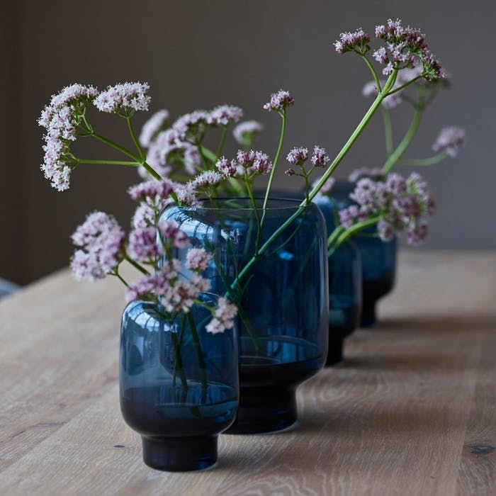 """Close-up of lilac flowers in blue vases.<span class=""""sr-only""""> (opened in a new window/tab)</span>"""
