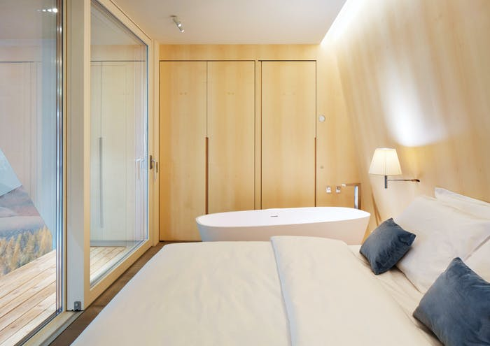 """The interior of EDEN luxury portable suite, an example of sustainable living and energy efficiency. View of bed, bathtub and hidden storage wall.<span class=""""sr-only""""> (opened in a new window/tab)</span>"""
