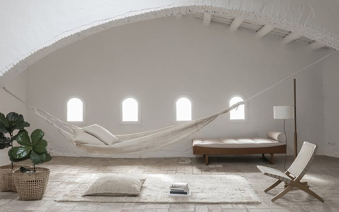 """White room with a hammock hanging from wall to wall.<span class=""""sr-only""""> (opened in a new window/tab)</span>"""