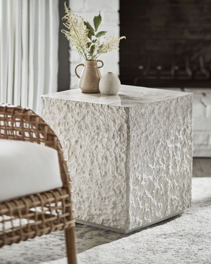 """Close-up view of a side table with a rich hammered texture and a rattan chair.<span class=""""sr-only""""> (opened in a new window/tab)</span>"""