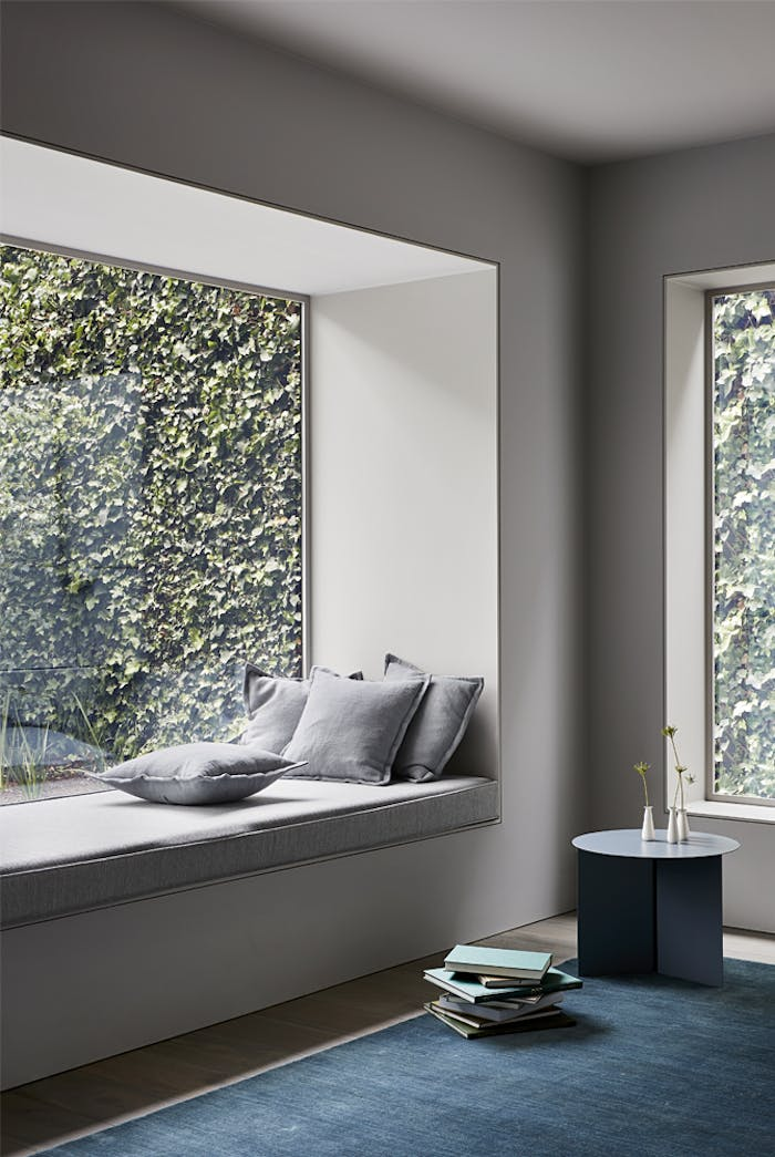 """Window seat looking into a wall of climbing vines.<span class=""""sr-only""""> (opened in a new window/tab)</span>"""