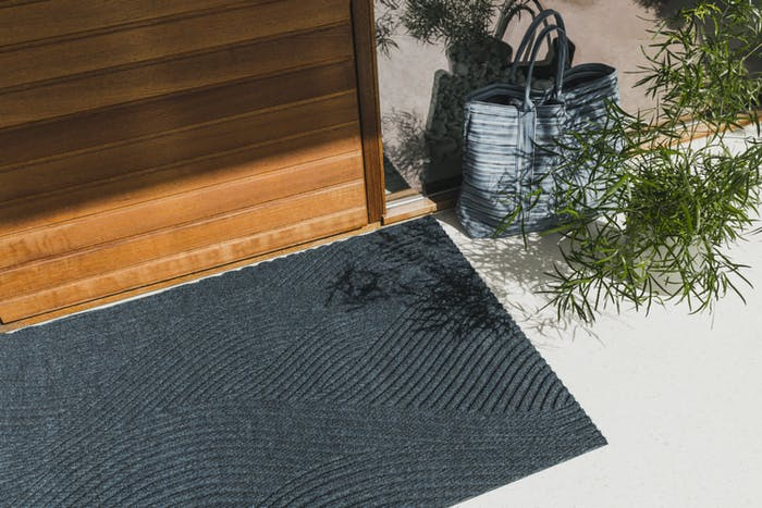 "Doormats styled next to a plant and a bag.<span class=""sr-only""> (opened in a new window/tab)</span>"