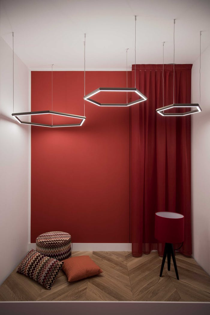 """Hexagonal pendant lights hanging from the wall in a changing room with a focal back wall painted in red.<span class=""""sr-only""""> (opened in a new window/tab)</span>"""