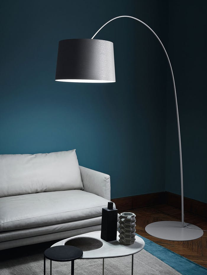 """Close-up of a white sofa with a big floor lamp over it.<span class=""""sr-only""""> (opened in a new window/tab)</span>"""