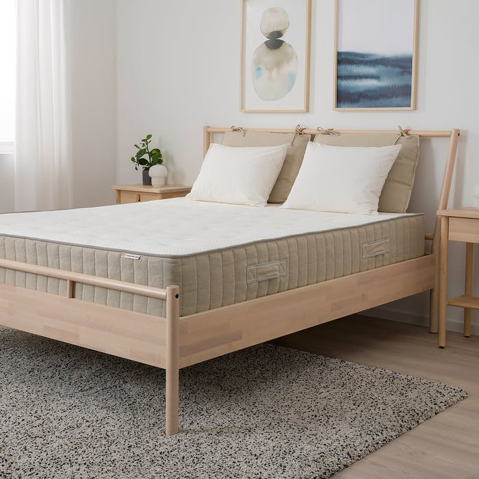 """Soothing bedroom with wood bed & nightstand and Nordic décor.<span class=""""sr-only""""> (opened in a new window/tab)</span>"""