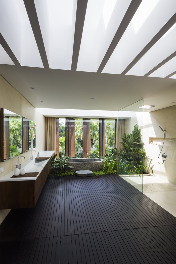 "Bathroom facing a huge window with plenty of plants down the bathtub.<span class=""sr-only""> (opened in a new window/tab)</span>"