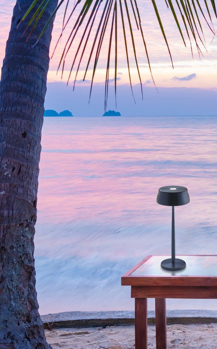 "Portable table lamp on a table facing the sea at sunset.<span class=""sr-only""> (opened in a new window/tab)</span>"