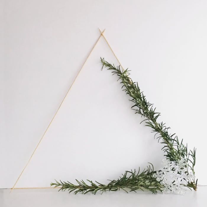 """Triangular wooden wreath decorated with rosemary twigs.<span class=""""sr-only""""> (opened in a new window/tab)</span>"""