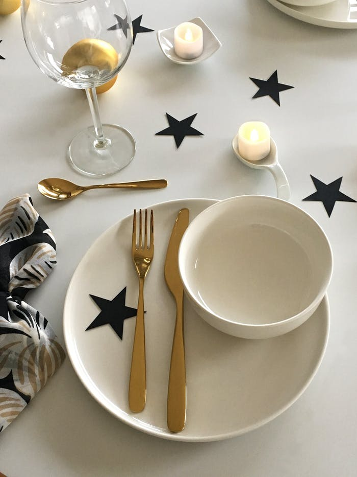 """Minimal Christmas table setting with white black cardboard stars and candles as a decor.<span class=""""sr-only""""> (opened in a new window/tab)</span>"""