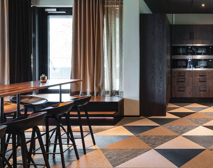 """Dining space with recycled vinyl floor in a pattern that resembles wood.<span class=""""sr-only""""> (opened in a new window/tab)</span>"""