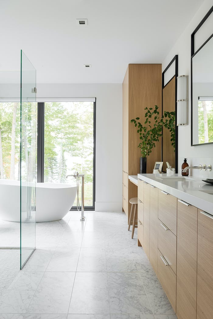 "A relaxing bathroom full of sunlight, natural materials and full-height windows looking into nature.<span class=""sr-only""> (opened in a new window/tab)</span>"
