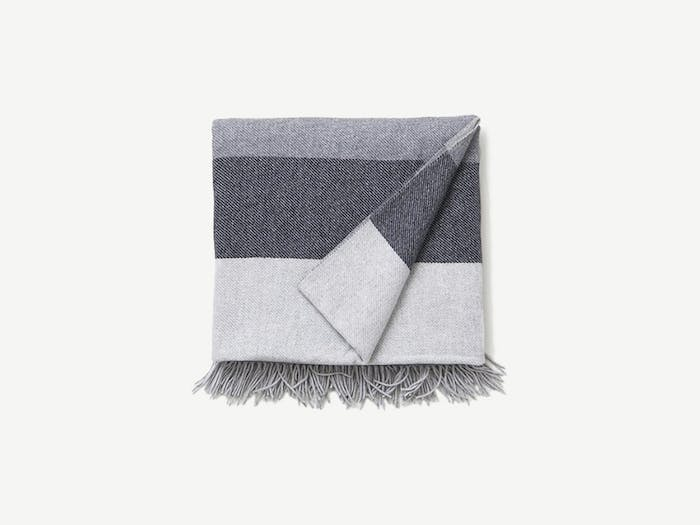"""Striped blanket in different shades of grey.<span class=""""sr-only""""> (opened in a new window/tab)</span>"""