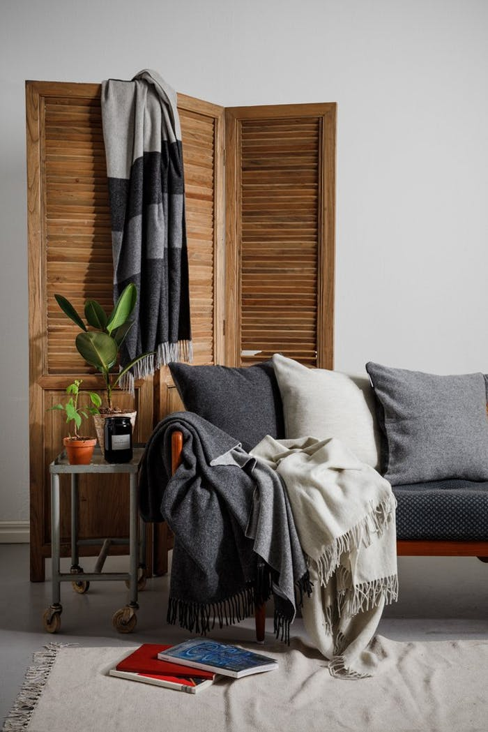 """Shot of the blanket on a sofa with some more accessories around.<span class=""""sr-only""""> (opened in a new window/tab)</span>"""