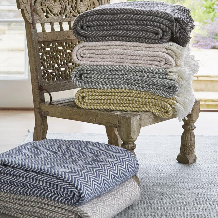 """A pile of blanket stacked onto a Moroccan style low chair.<span class=""""sr-only""""> (opened in a new window/tab)</span>"""