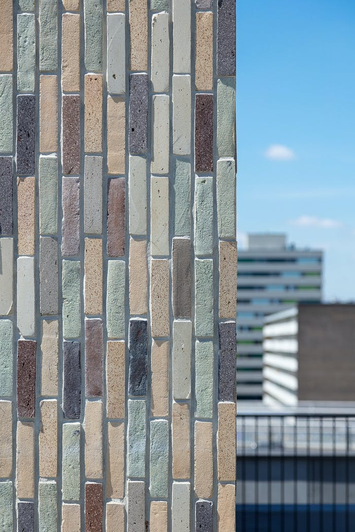 """Close-up of the colourful waste-based bricks covering.<span class=""""sr-only""""> (opened in a new window/tab)</span>"""