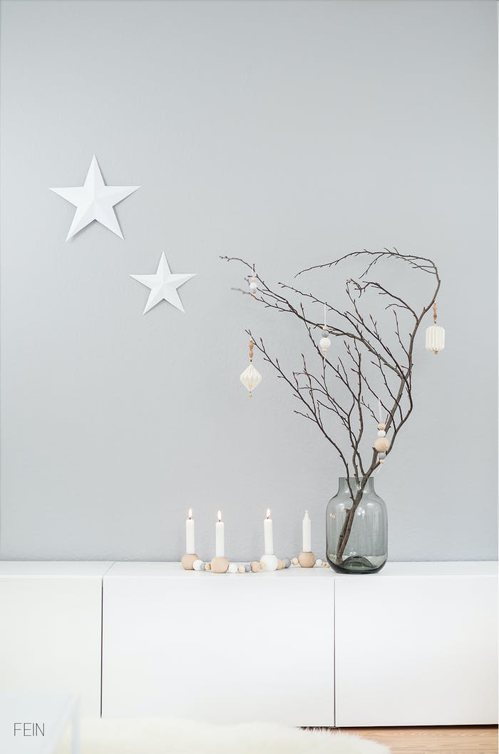 """Branch decorated with white ornaments on a light grey wall background.<span class=""""sr-only""""> (opened in a new window/tab)</span>"""