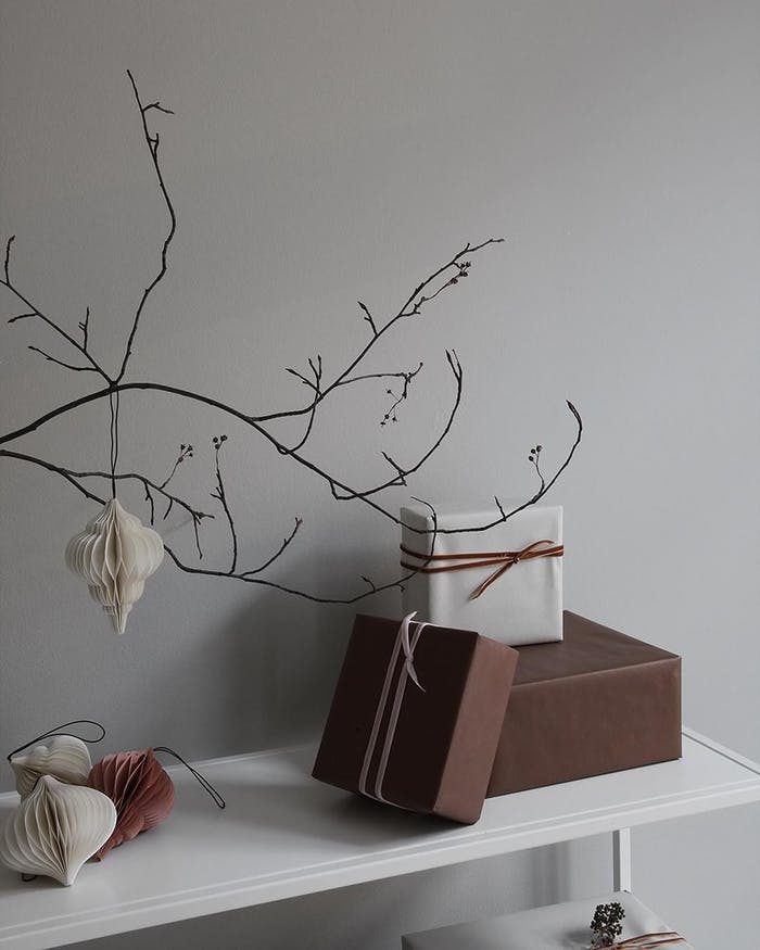 """Branch decorated with paper ornaments in earthy tones.<span class=""""sr-only""""> (opened in a new window/tab)</span>"""