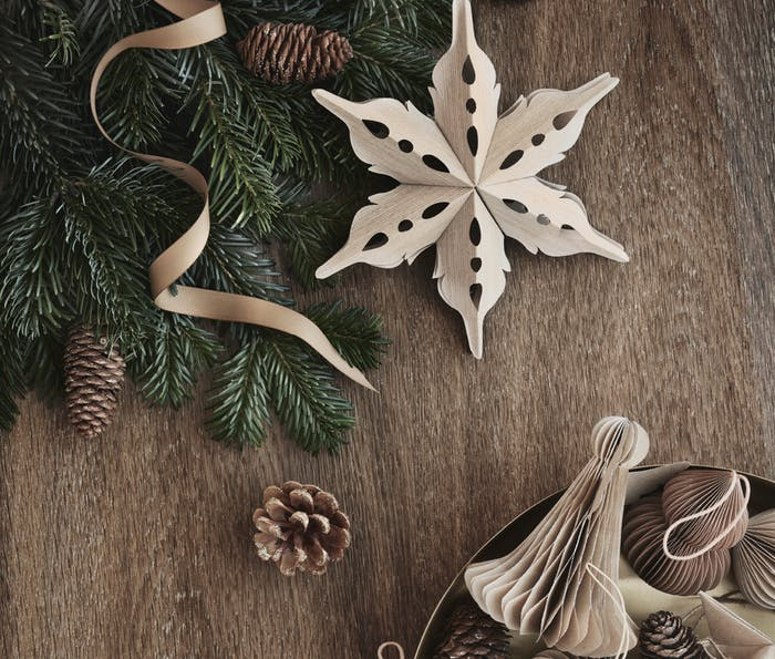 """Paper sustainable Christmas ornaments on a wood background.<span class=""""sr-only""""> (opened in a new window/tab)</span>"""