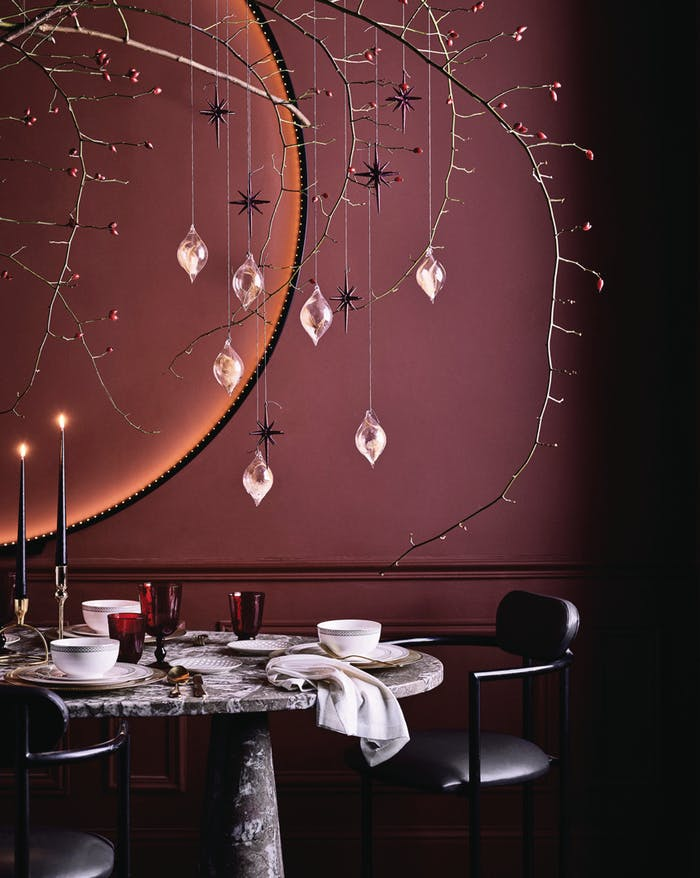 "Branch with Christmas ornaments hung over a modern dining table.<span class=""sr-only""> (opened in a new window/tab)</span>"