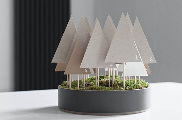 """Advent calendar made of paper trees mounted on a wooden stick and tucked in a container onto a moss base.<span class=""""sr-only""""> (opened in a new window/tab)</span>"""