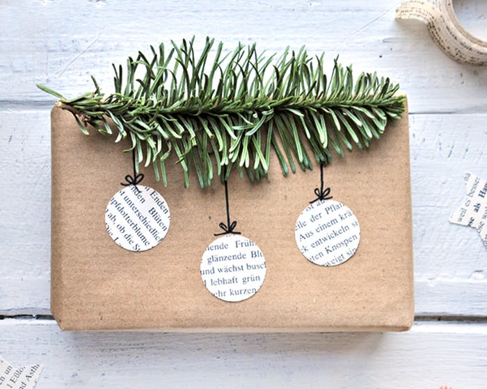 """Gift wrapped in brown paper and decorated with newspaper cut-outs in the shape of Christmas ornaments hanging from a fluffy twig of greenery.<span class=""""sr-only""""> (opened in a new window/tab)</span>"""