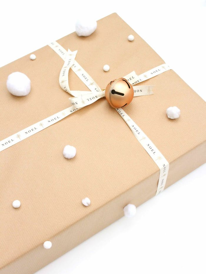"Brown paper gift wrapping decorated with a small bell and white fabric pompoms all around.<span class=""sr-only""> (opened in a new window/tab)</span>"
