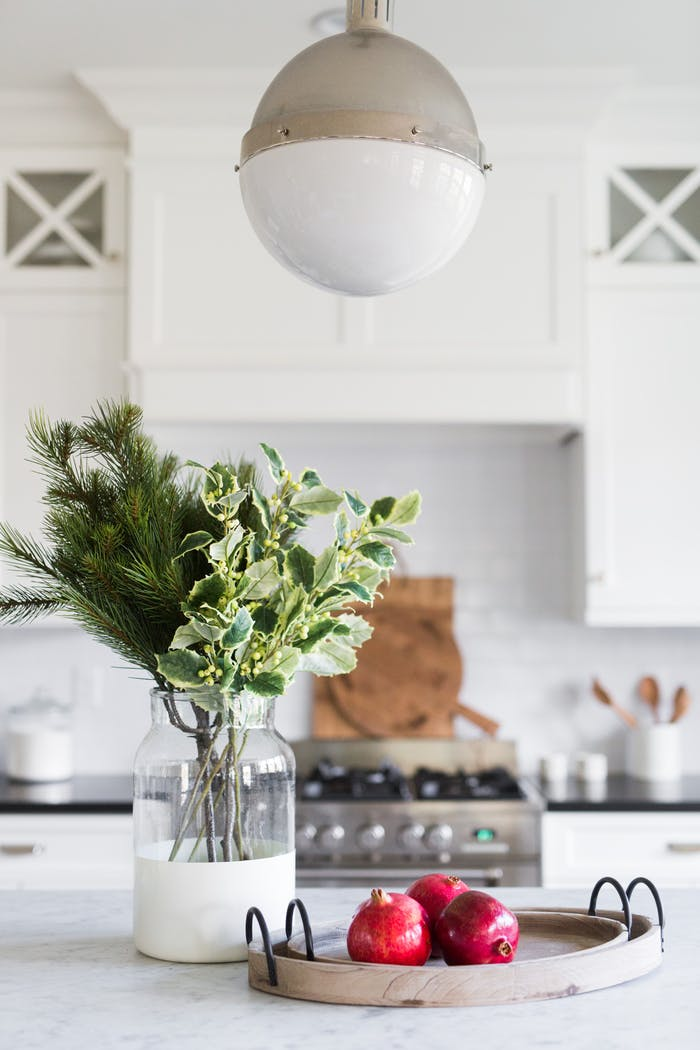 """Real twigs on a vase and few pomegranates make for an understated decoration of the kitchen counter.<span class=""""sr-only""""> (opened in a new window/tab)</span>"""